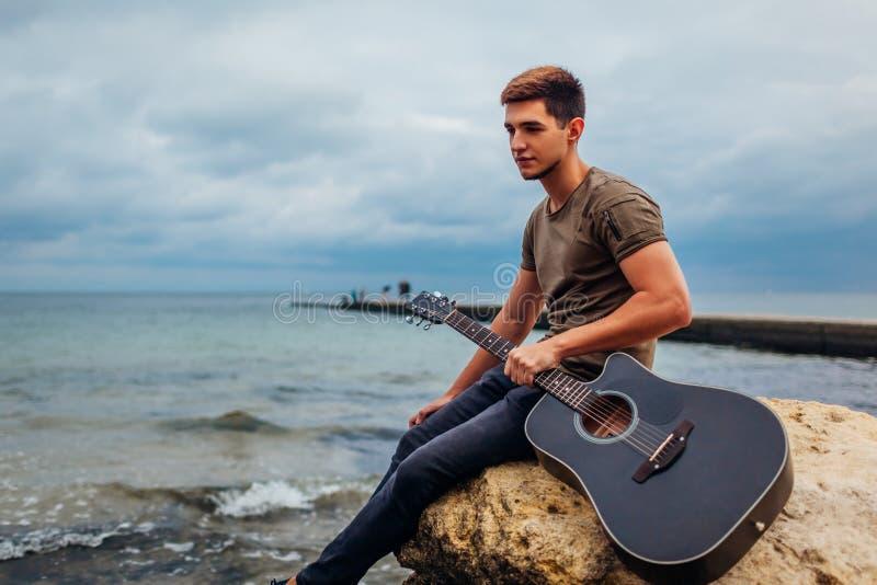 Wzburzona młodego człowieka mienia gitara akustyczna na plaży otaczającej z skałami na deszczowym dniu Czuciowy smutny i osamotni fotografia royalty free