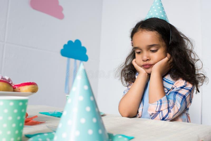 wzburzona mała amerykanin afrykańskiego pochodzenia dziewczyna siedzi samotnie przy urodziny obraz royalty free