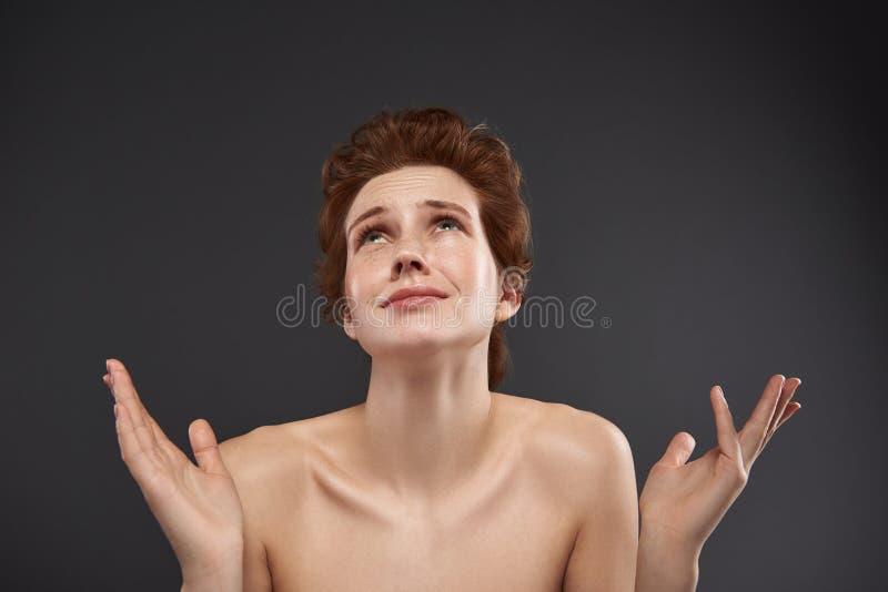 Wzburzona miedzianowłosa dziewczyna przyglądająca w górę rozpacza w obrazy royalty free