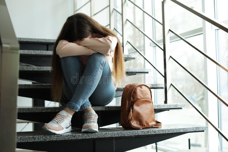 Wzburzona nastoletnia dziewczyna z plecaka obsiadaniem na schodkach zdjęcia royalty free