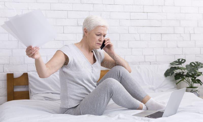 Wzburzona starsza kobieta opowiada na telefonie i działaniu w domu obrazy stock