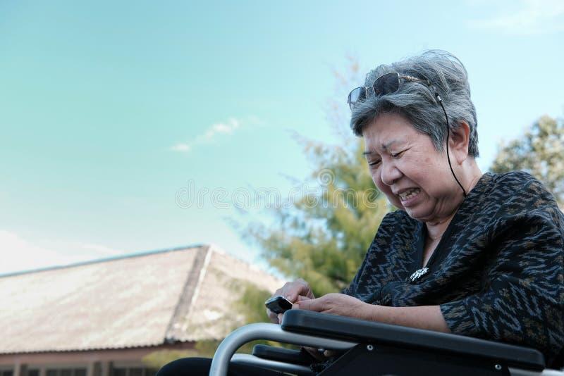 wzburzona starszej osoby kobieta na wózka inwalidzkiego mienia telefonie komórkowym starszej osoby se obraz stock