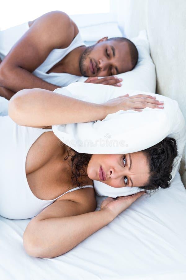 Wzburzony żony dosypianie oprócz chrapa męża zdjęcie royalty free