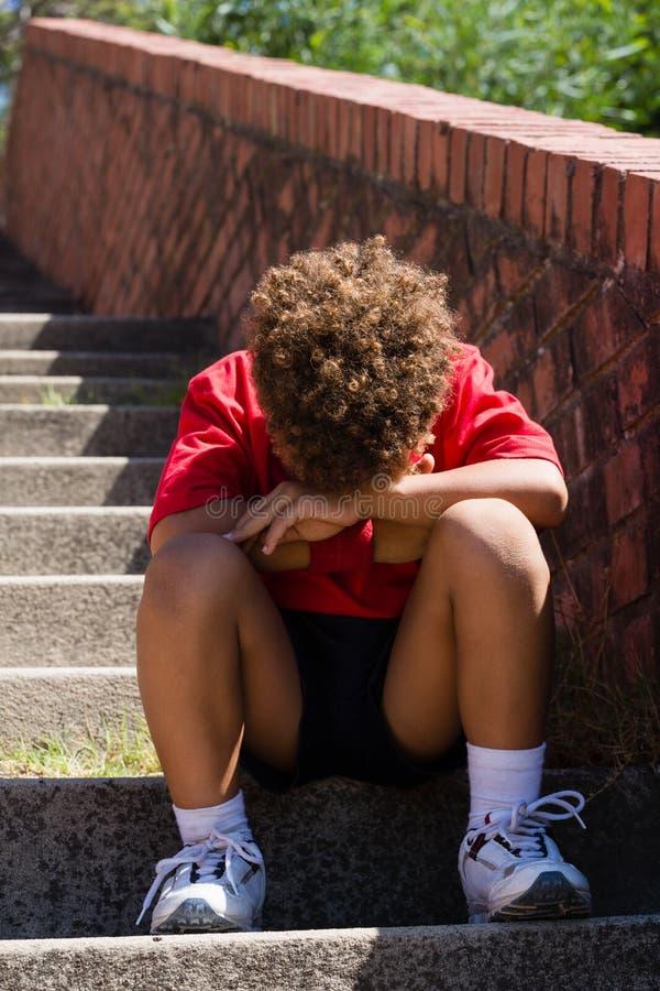 Wzburzony chłopiec obsiadanie na schody w obóz dla rekrutów obraz stock
