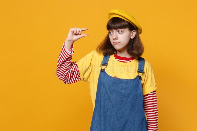Wzburzony dziewczyna nastolatek w francuskim berecie, drelichowi sundress gestykuluje demonstrujący rozmiar z workspace odizolowy zdjęcie stock