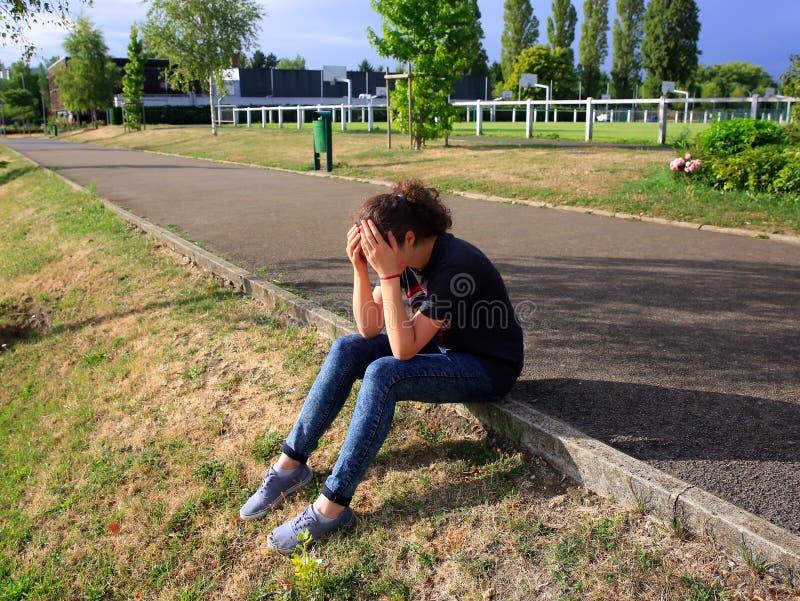 Wzburzony dziewczyny obsiadanie w szkolnym jardzie zdjęcie royalty free