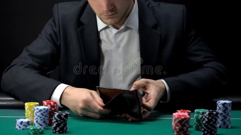 Wzburzony hazardzista patrzeje w pustym portflu, nieudacznik przy kasyno stołem, gemowy nałóg obrazy stock