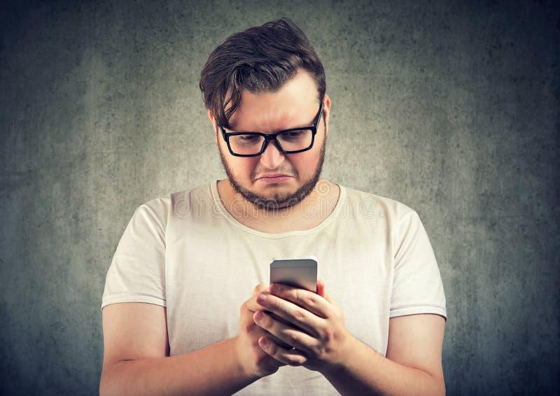 Wzburzony mężczyzna dopatrywanie przy smartphone obraz royalty free