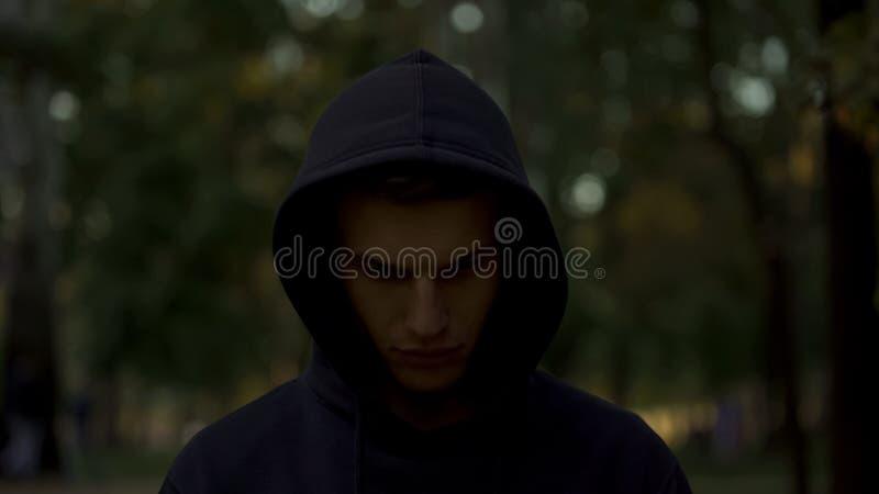 Wzburzony mężczyzna patrzeje w dół, czuje winny i żałuje przestępcy za w kapiszonie, zdjęcie stock