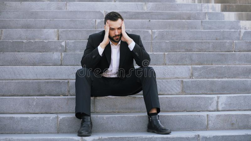Wzburzony młody biznesowy mężczyzna ma stres i obsiadanie na schodkach w ulicie Biznesmen ma dylowego problemu pojęcie obrazy royalty free