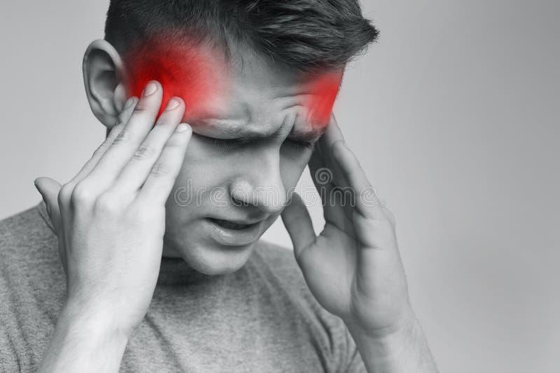 Wzburzony młody człowiek gniesie głowę z rękami, cierpi od migreny fotografia stock