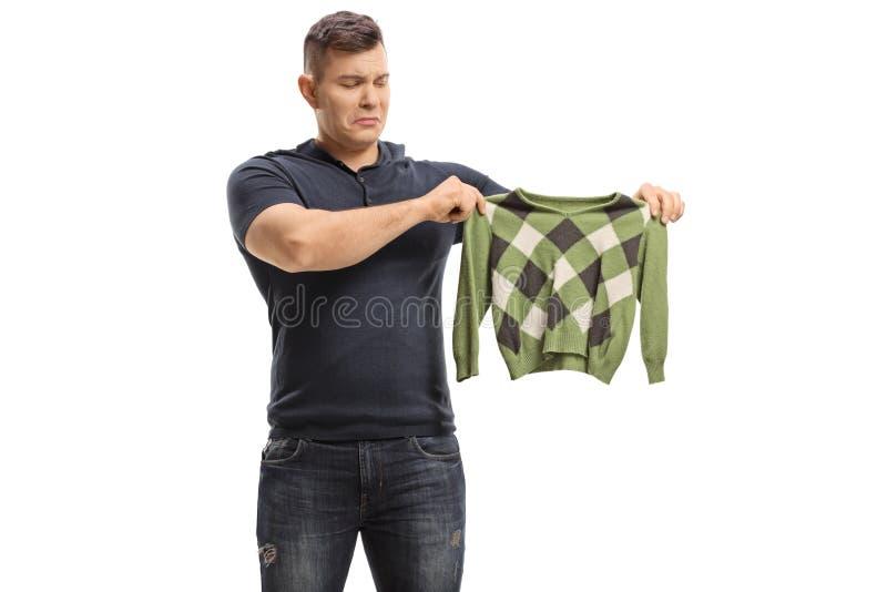 Wzburzony młody człowiek z kurczącą się bluzką obraz royalty free