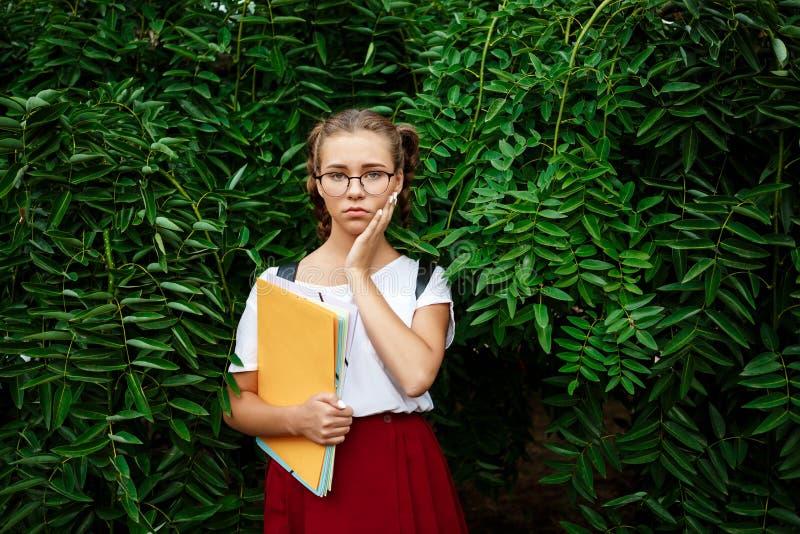 Wzburzony młody piękny żeński uczeń trzyma falcówki outdoors w szkłach, parkowy tło fotografia royalty free