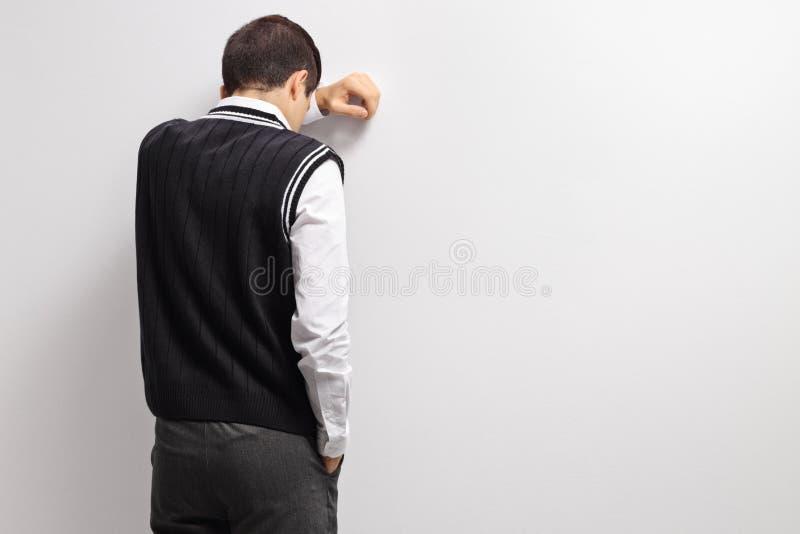 Wzburzony nastoletni uczeń z jego głową przeciw ścianie fotografia stock