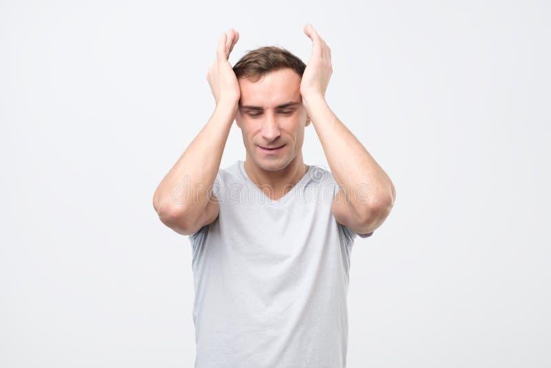Wzburzony nieszczęśliwy młody włoski mężczyzna gniesie głowę z rękami, cierpi od migreny fotografia stock