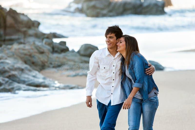 Wzdłuż plaży pary śliczny nastoletni odprowadzenie. obraz royalty free