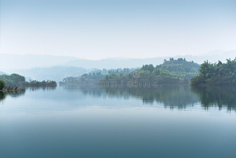 Wzgórza z drzewami w mgle od jeziora w Chiny zdjęcia royalty free