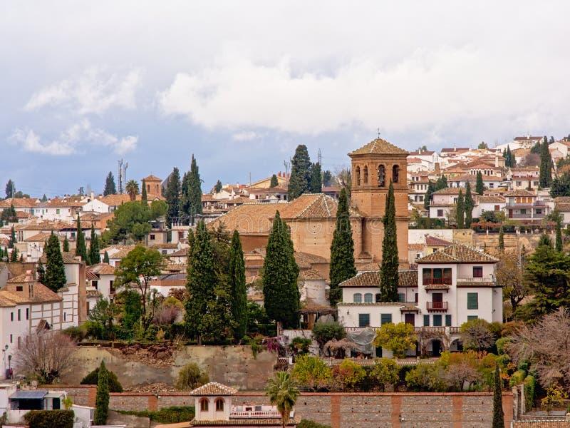 Wzgórze flanka Albayzin neighbourhood, Granada, z rzymskim kościół na odgórnych i białych traditionnal domach na skłonach fotografia royalty free