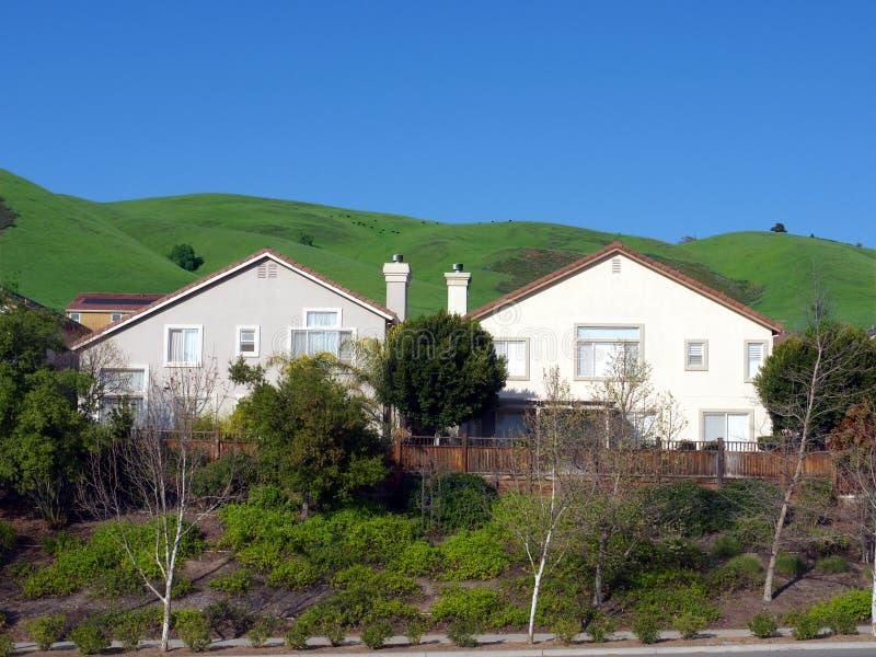 wzgórze zieleni domy identyczni dwa obrazy stock