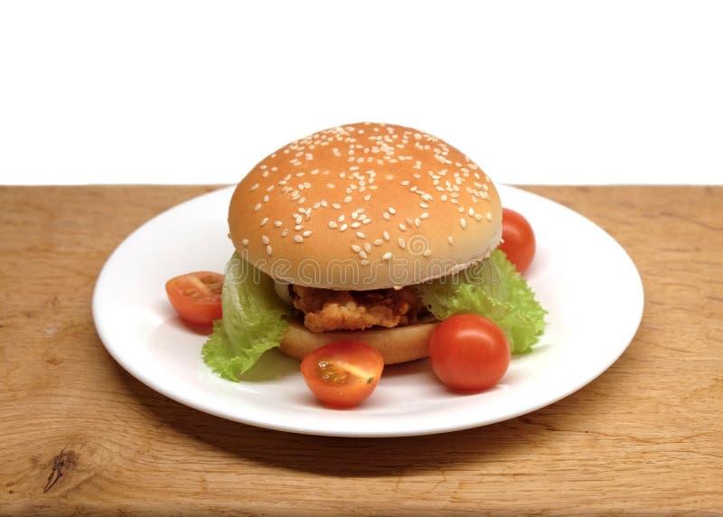 Wzmacnia hamburger z sałatkowymi i małymi pomidorami na talerzu fotografia stock