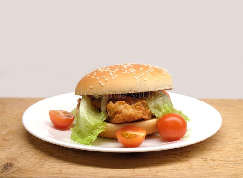Wzmacnia hamburger z sałatkowymi i małymi pomidorami na talerzu obraz stock