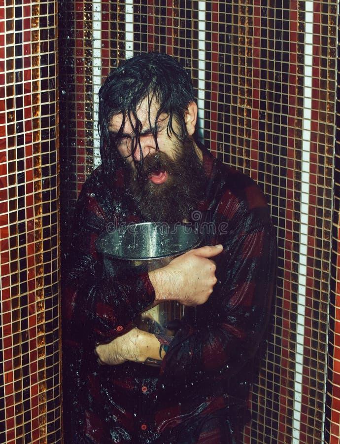 Wzmacniający przystojny mężczyzna, brodaty modniś z brodą i wąs w czerwonej w kratkę koszula mokrej z wodą w prysznic z, zdjęcie stock