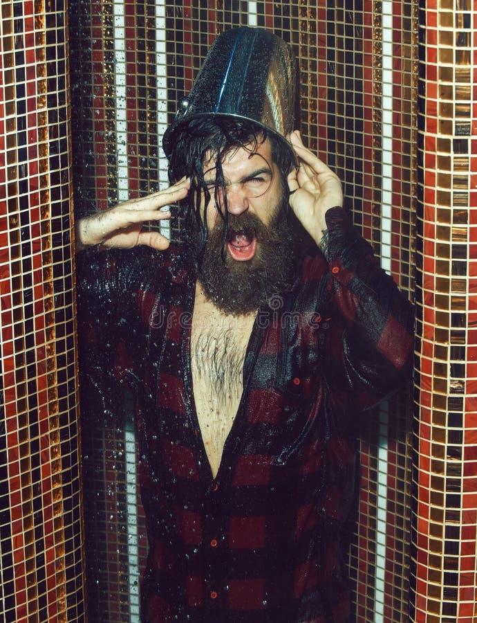 Wzmacniający przystojny mężczyzna, brodaty modniś z brodą i wąs w czerwonej w kratkę koszula, nalewamy wiadro woda na głowie wewn obraz stock