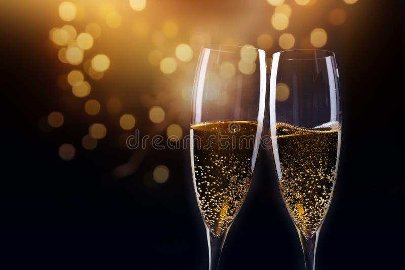 wznosić toast z szampańskimi szkłami przeciw wakacyjnym światłom i nowemu y obraz royalty free