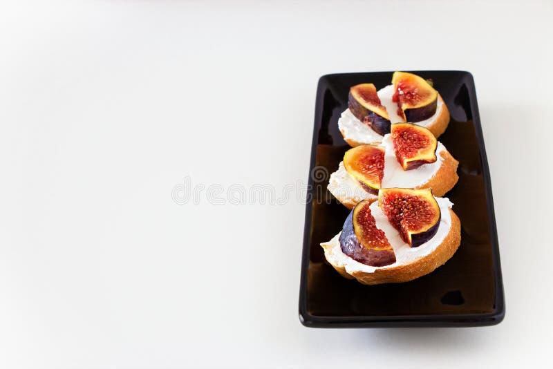 Wznosi toast Bruschetta z świeżą figą, Koźli ser na czarnym talerzu Whi obrazy stock