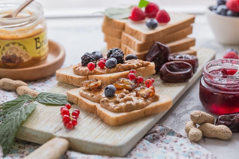 Wznosi toast chleb z domowej roboty truskawkowym dżemem i masłem orzechowym słuzyć z jagodą Odgórny widok zdjęcie royalty free