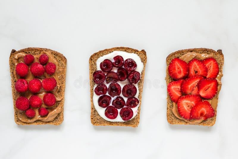 Wznosi toast chleb z masłem orzechowym i miękkim serem z jagodami na bielu marmuru stole zdrowe śniadanie obrazy royalty free