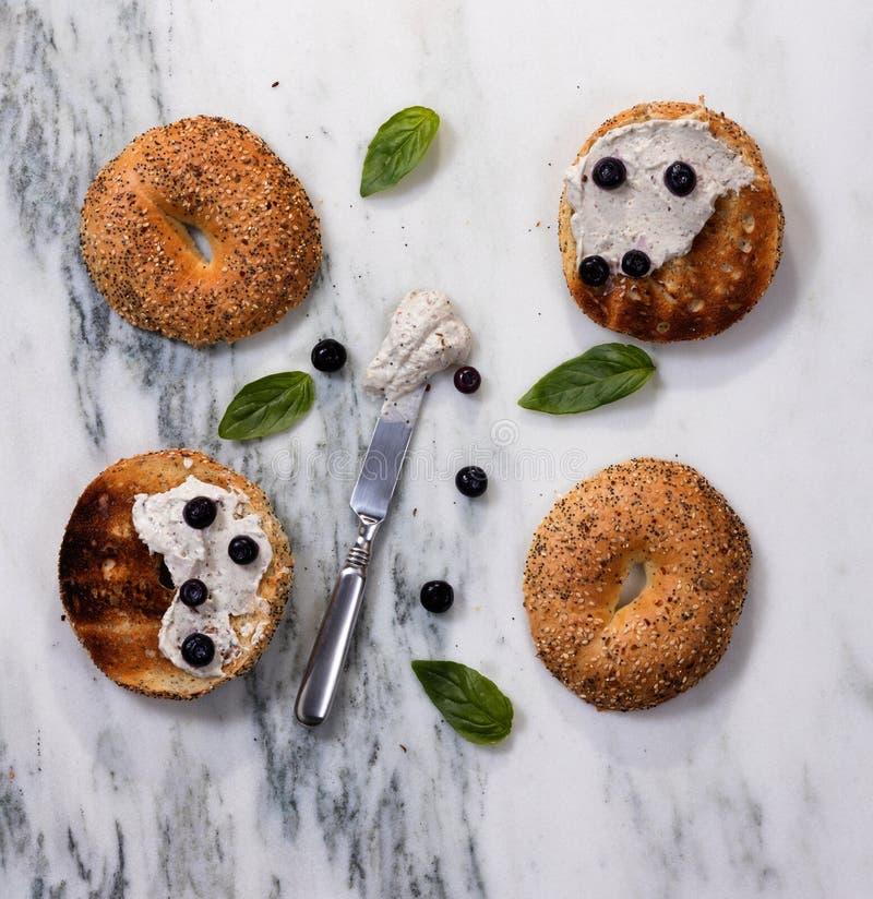Wznoszący toast bagels z kremowym serem i ziele na marmurowym countertop zdjęcia stock
