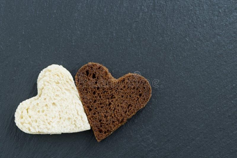 Wznoszący toast biały chleb w postaci serca i żyto zdjęcie royalty free