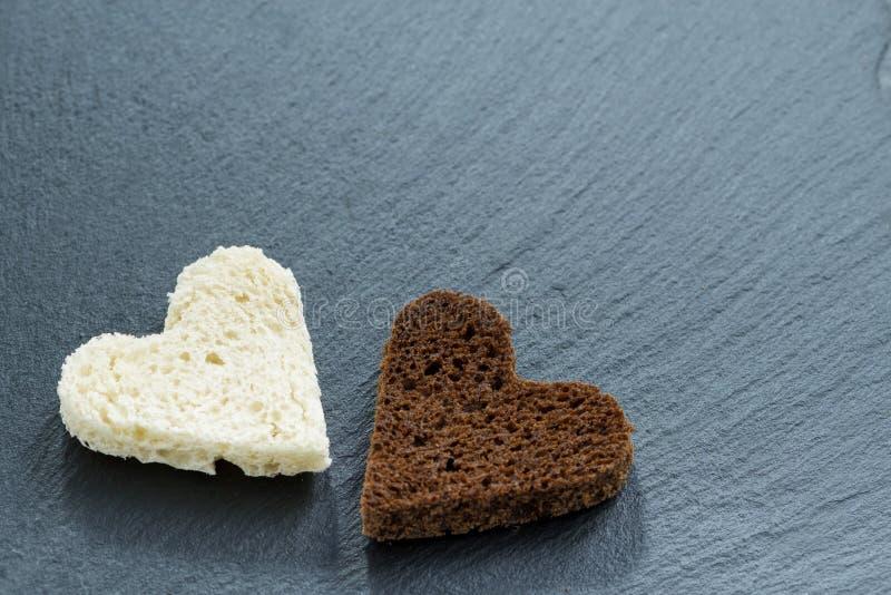 Wznoszący toast biały chleb w postaci serca na czerni i żyto zdjęcie stock