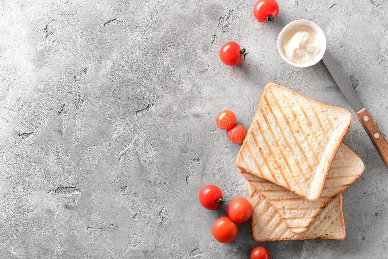 Wznoszący toast chleb, kremowy ser i czereśniowi pomidory na popielatym tle, odgórny widok zdjęcie royalty free