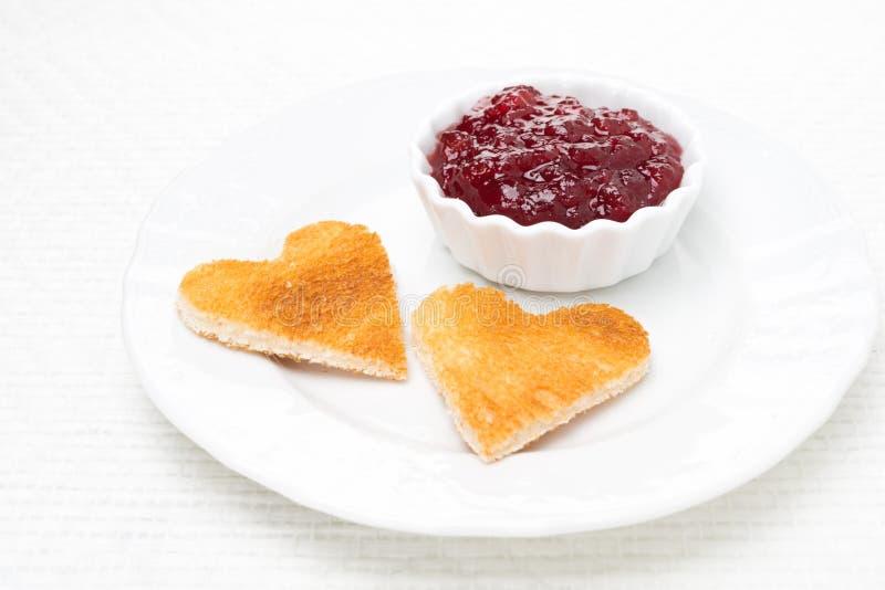 Wznoszący toast chleb w formie serca z jagodowym dżemem na talerzu fotografia royalty free