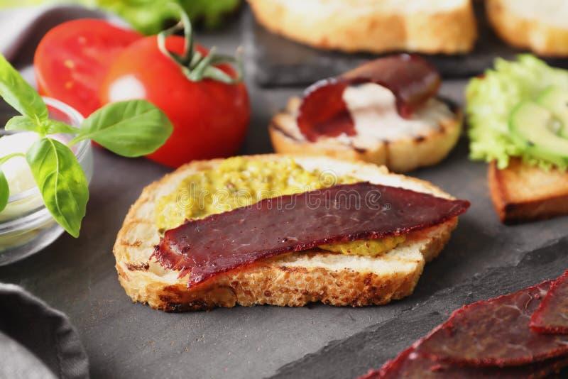 Wznoszący toast chleb z mięsem na stole zdjęcie royalty free