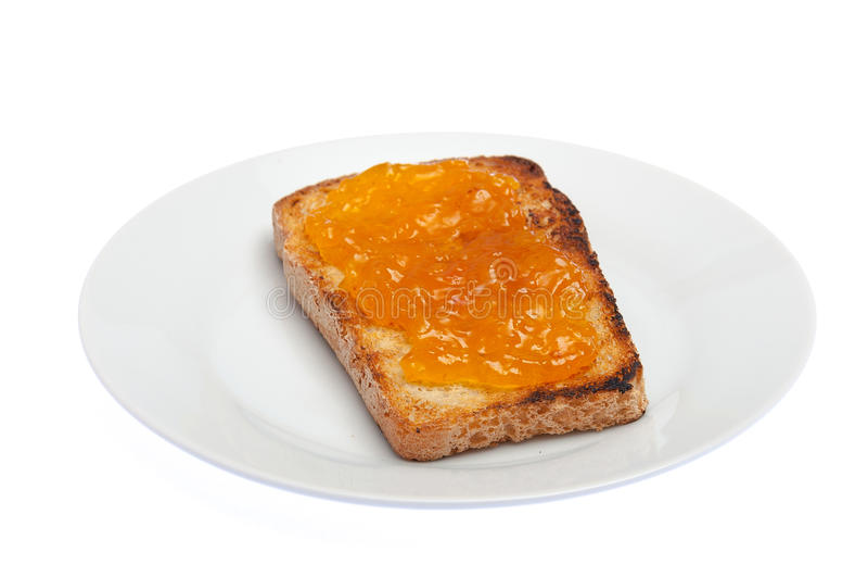 Wznoszący toast chleb z morelowym dżemem odizolowywającym na bielu Zdrowy breakf obrazy stock