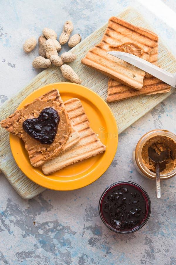 Wznoszący toast chleb z truskawkowym dżemem w formie serca w talerzu na starym drewnianym stole, odgórny widok zdjęcie stock