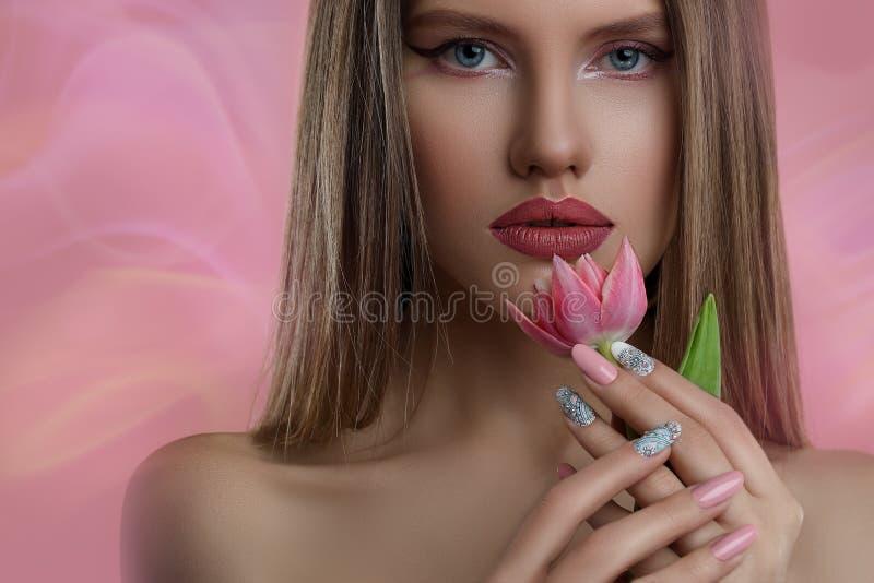 Wzorcowa dziewczyna z fachowym makijażem i gwóźdź sztuka robimy manikiur nad różowym tłem fotografia royalty free