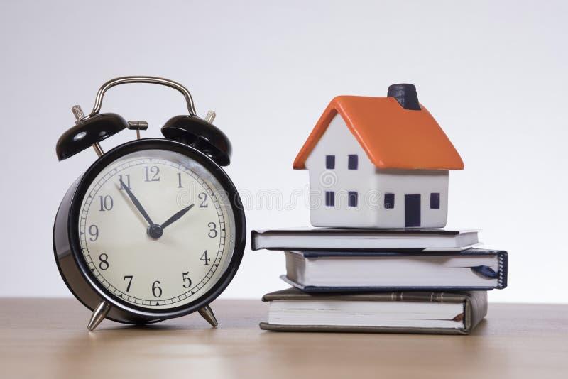 Wzorcowy dom, książki i cykota zegarowy pojęcie, zdjęcia royalty free
