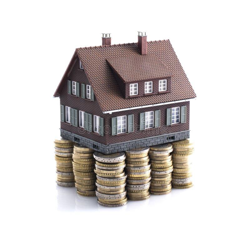 Wzorcowy dom z stosami monety jako podstawa zdjęcia royalty free