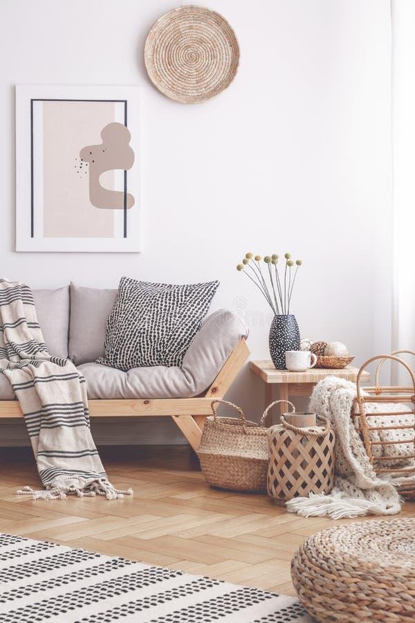 Wzorzysta koc na drewnianej leżance w białym żywym izbowym wnętrzu z plakatem i koszami Istna fotografia obraz royalty free