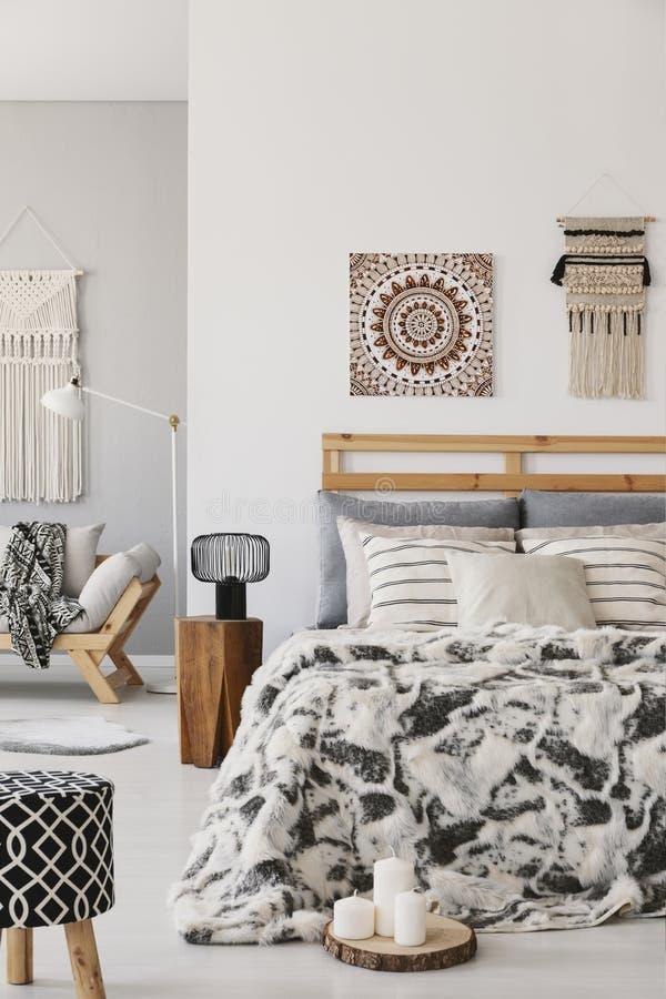Wzorzysta stolec i lampa obok łóżka z poduszkami w scandi sypialni wnętrzu z plakatem obrazy stock