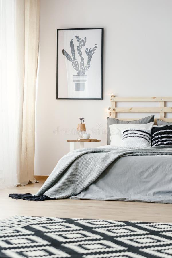 Wzorzysty dywan i plakat w popielatym prostym sypialni wnętrzu z obrazy stock