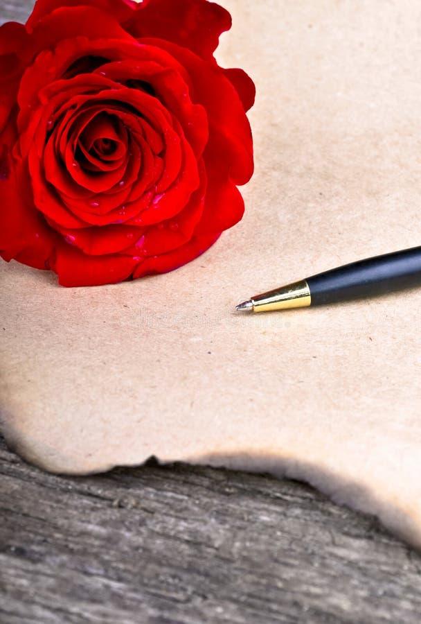 Wzrastał kwiatu i listu miłosnego na drewnianym tło valentines dniu fotografia stock