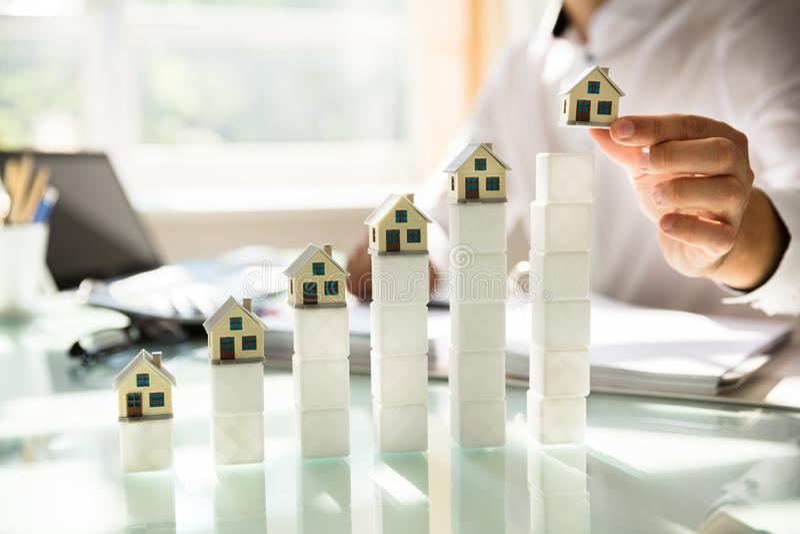 Wzrastaj?cy dom?w modele na odbijaj?cym biurku obrazy stock