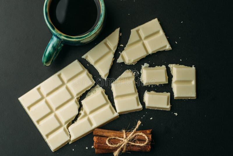 Xícara de café, barra de chocolate branca quebrada e pilha de canela na tabela preta, vista superior Alimento saboroso da caloria fotografia de stock