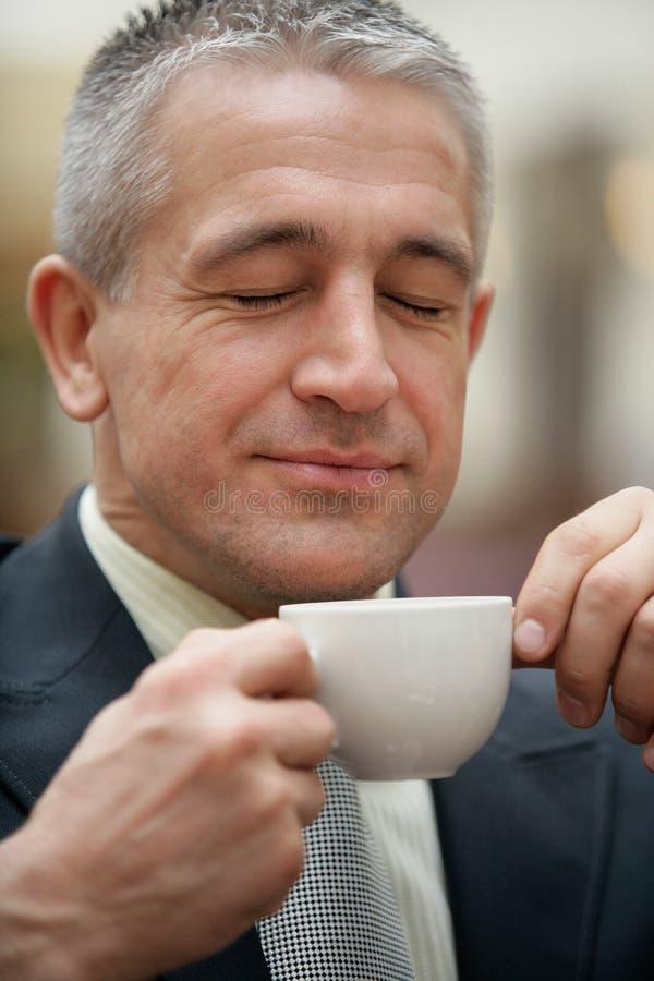 Xícara de café bebendo do homem de negócios superior considerável fotografia de stock