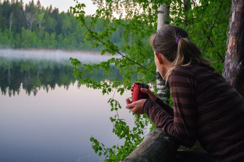 Xícara de café bebendo ou chá da moça bonita a aquecer-se A mulher atrativa do retrato olha pensativamente para fora sobre o lago fotografia de stock royalty free